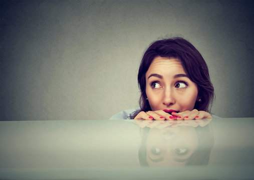 worried young woman looking at something peeking from under the table