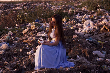 Girl on the landfill holds the broken cup