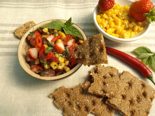 Salsa with strawberries and corn, dried rye bread. Mexican food.