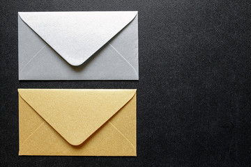 gold and silver envelopes on black background