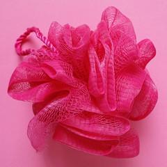 pink bath puff or sponge on pink background