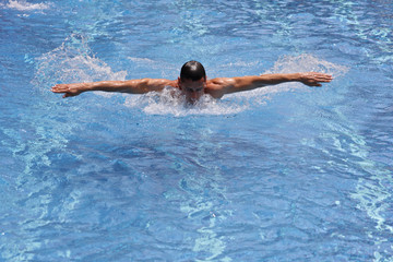 Sporty, athletic man, strong, muscular body swimming in pool style.