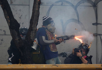 A demonstrator uses a homemade mortar while clashing with riot security forces during a rally against Venezuela's President Nicolas Maduro's government in Caracas