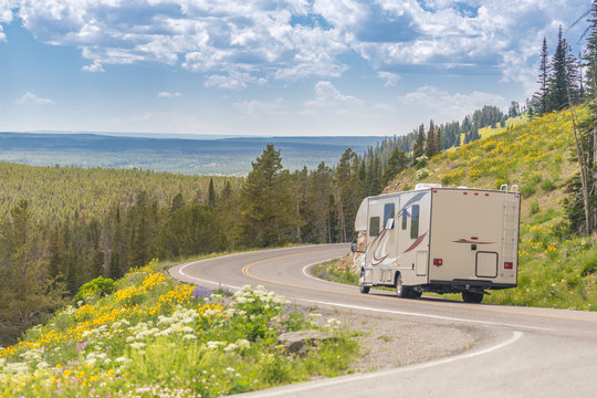 Camper Driving Down Road in The Beautiful Countryside Among Pine Trees and Flowers.