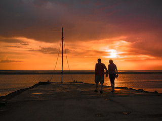 Couple walking on jetty in the sunset