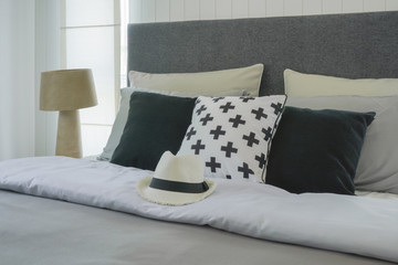 Hat on bed with pillows in stylish bedroom interior