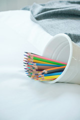 Color pencils in white cup lay on white background