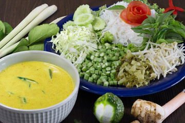 Thai rice noodle eaten with curry and veg. thai food (Thai language Kanom jeen) on blue dish and green bowl, All on brown wooden background / Selective focus..