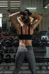 Asian woman works out with dumbbells in gym.