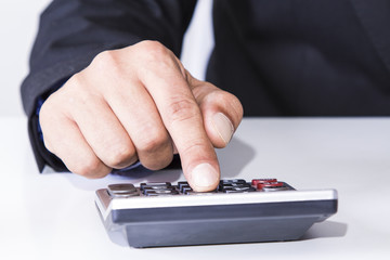 Businessman at office using calculator