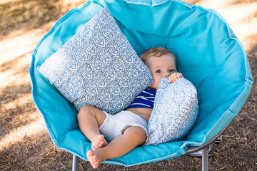 One year old little boy portrait on the blue garden armchair with pillow
