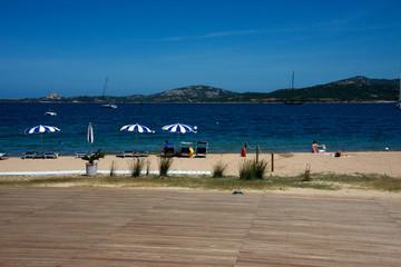 panorama marino a Cannigione Costa Smeralda con spiaggia di sabbia bianca, mare blu, vegetazione, ombrelloni da spiaggia.