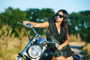 Sexy biker woman sitting on his motorcycle in the city. Beauty, fashion. Of adventure and freedom.