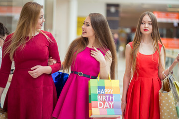 Women with high heels and shopping bags - Three girls сhatting after buying presents