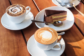 Two cups of hot Cappuccino coffee and chocolate mousse cake