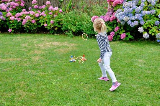 Une jeune fille lance un anneau dans une cible