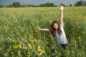 asian women with slightly curly is raising arms to the sky  in yellow field at summer, Thailand.