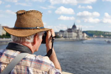 Senior pensioner tourist photographing Budapest panorama, Hungary