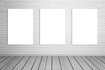 Three isolated art canvas on brick wall for mockup. Empty gallery space. Wooden floor.