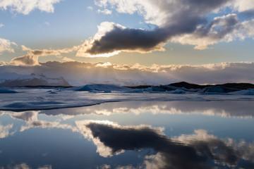 Sunlight behind white cloud over Jakulsarlon winter season lagoon, Iceland natural landscape background