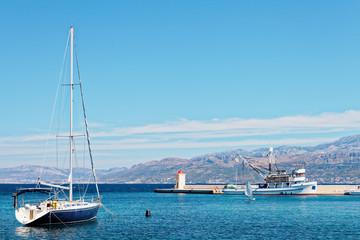 Moored yatch and a fishing trawler in the harbor of a small town Postira - Croatia, island Brac