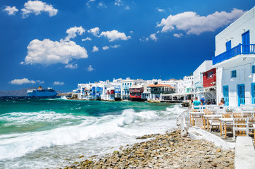 Little Venice, Mykonos island, Greece. Colourful buildings and balconies near the sea and a large white cruise ship.