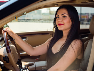 Portrait of a beautiful brunette that sits in a luxury car.