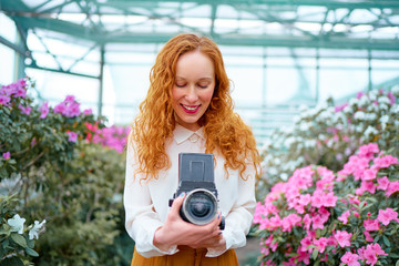 Pretty photographer. Attractive long hair young woman with camera taking pictures at blossom garden.