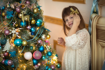 Girl kid in dress with  bear around  Christmas tree,  real interior, toning