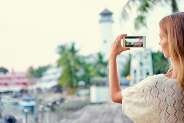 Tourism concept. Young woman  taking photo on smartphone while walking on the seafront.