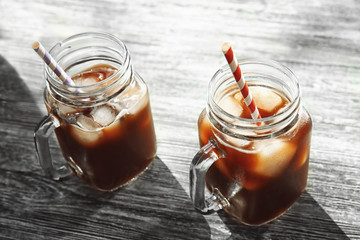 Mason jars with cold brew coffee and straws on wooden table