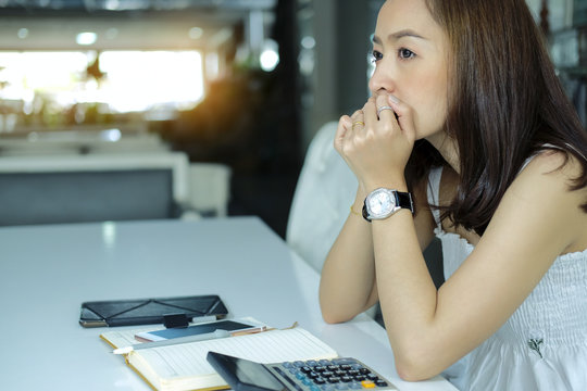 Sad Woman Sitting On chair With calculator And note book account by serious expenses