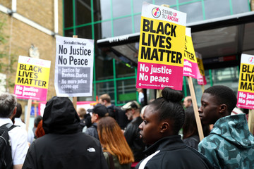 Demonstrators gather at a protest outside Stoke Newington police station over the death of Rashan Charles