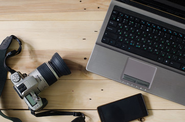Camera and laptop on wooden background.