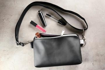 Leather handbag with cosmetics on light background