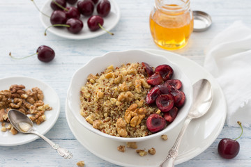 Healthy delicious vegan breakfast. Quinoa with fresh cherries, walnuts and honey on the blue background