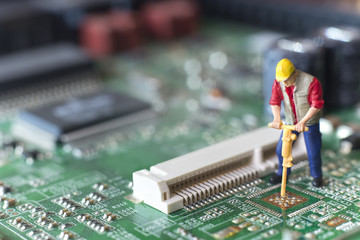 Miniature Worker Drilling On Top Of Circuit Board