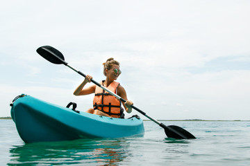 Happy young woman kayaking on the lake