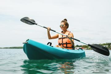 Happy young woman kayaking on the lake