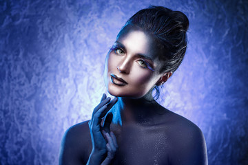 Beautiful woman with a creative makeup and body-art