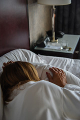 Woman laying in hotel bed sleeping next to alarm clock