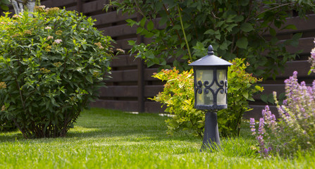 Garden lighting - lights on the solar battery on a green lawn next to a paved path