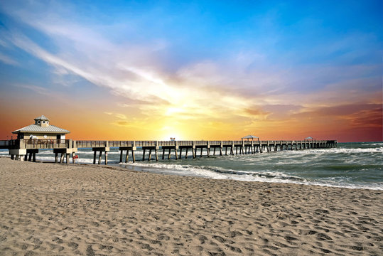 The Juno Beach Fishing Pier, Florida at sunrise on a windy summer day.