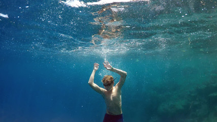 young man dives into the sea
