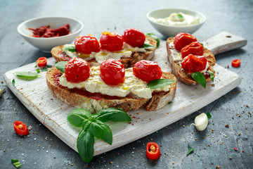 Tomato Ricotta Bruschetta with sun dried tomatoes paste, olive oil brown bread and basil in a white wooden board.