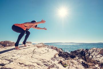 Woman has yoga practice on the deserted sea coast