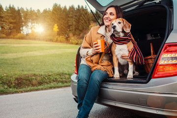 Woman and dog with shawls sits together in car trunk  on autumn road