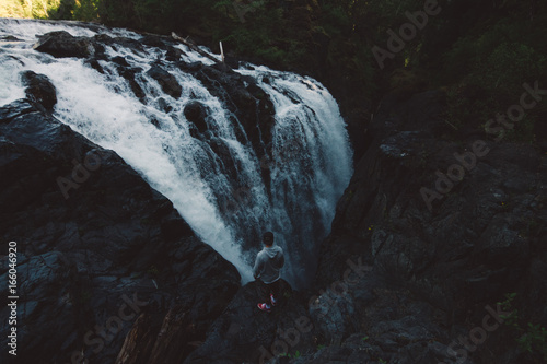 man standing on the edge of the cliff in forest with waterfall