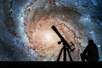 Man with telescope looking at the stars. Pinwheel Galaxy Messier 101, M101 in the constellation Ursa Major.