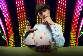 Beautiful young man on a beautiful background playing poker. Good luck in card games on the big money.